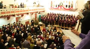 The audience joins the choir in carol singing, Christmas 2013